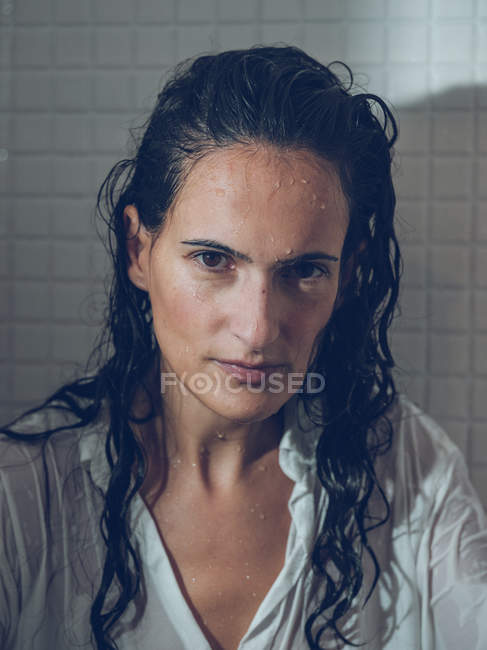 Sopping woman in shirt sitting in shower and looking at camera — Stock Photo