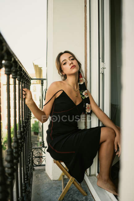 Charming young lady in dress posing on balcony — Stock Photo