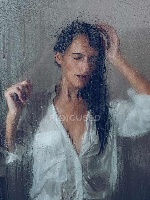Sopping woman in shirt posing in shower cabin — Stock Photo