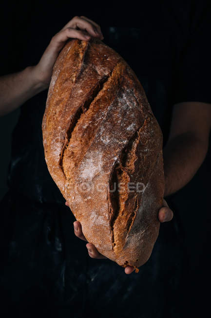 Human hands holding homemade rustic bread loaf — Stock Photo