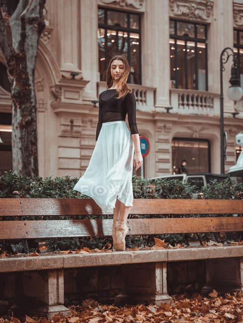 Молодая балерина, стоящая на цыпочках на скамейке на улице — стоковое фото