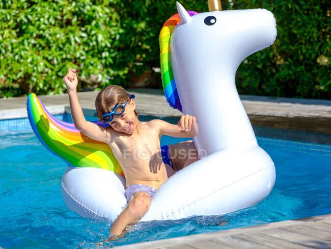Boy swimming on unicorn float — Stock Photo