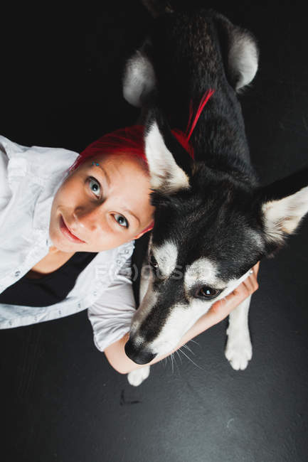 Portrait of young woman hugging puppy of adorable Siberian Husky on black background — Stock Photo