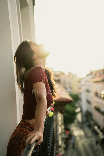 Charming young brunette lady relaxing on balcony — Stock Photo