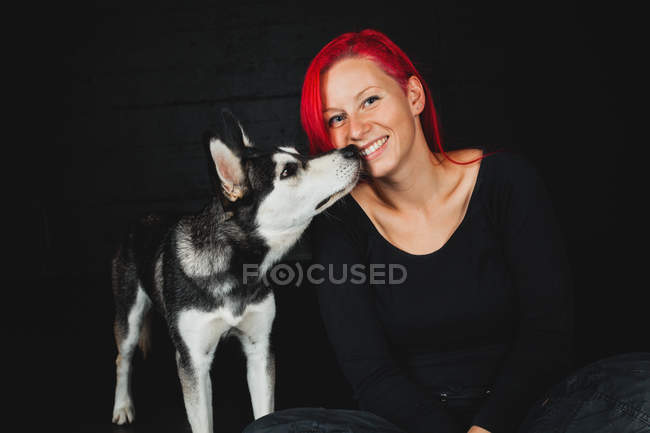 Portrait of young woman sitting with puppy of adorable Siberian Husky on black background — Stock Photo