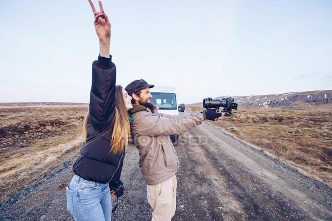Vue latérale dame souriante avec la main vers le haut près du gars prenant selfie sur la caméra près de la voiture sur la route entre les terres sauvages en Islande — Photo de stock