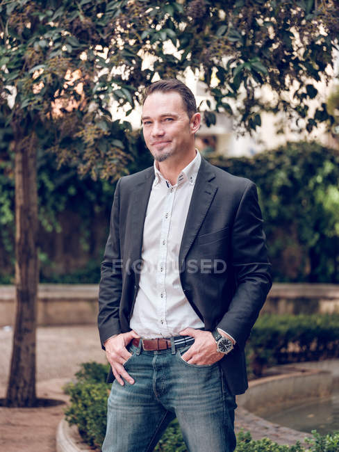 Handsome man in elegant jacket smiling and looking away while standing in park — Stock Photo