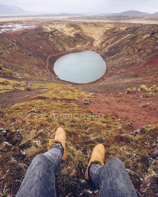 From above crop human legs near lake in crater between death brown lands and hills in Iceland — Stock Photo