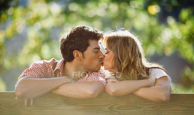 Jeune homme et femme embrassant dans des vêtements autrichiens traditionnels sur le banc sur fond flou de jardin — Photo de stock