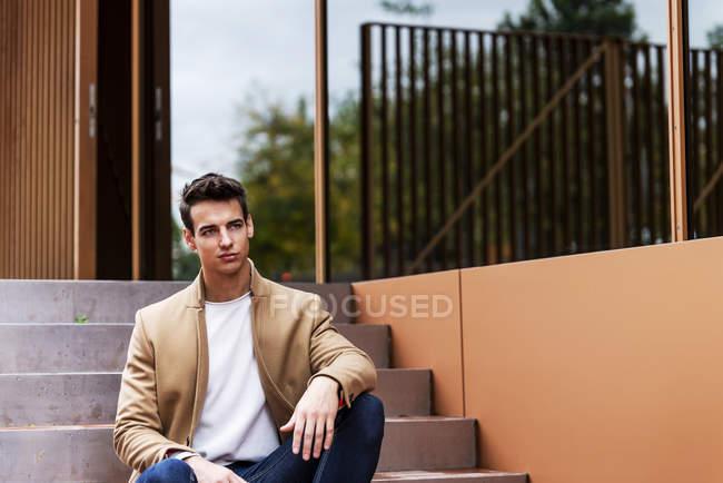 Ritratto di giovane elegante con cappotto seduto su una scala — Foto stock