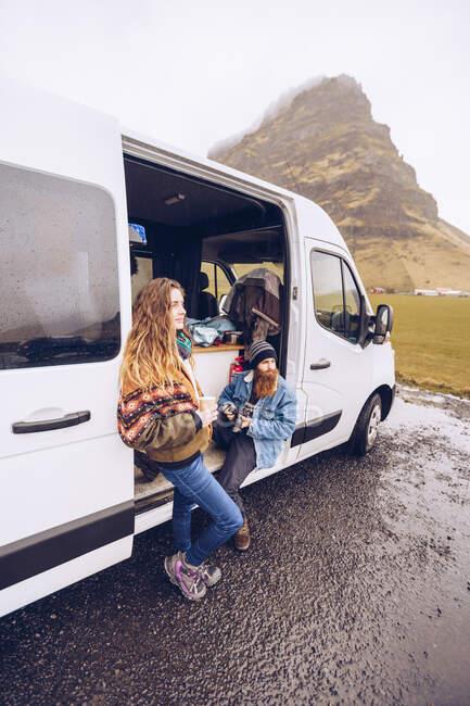 Бородатый парень и привлекательная дама в теплой одежде с кружкой глядя на открытую дверь фургона рядом с Скалистым холмом в Исландии — стоковое фото