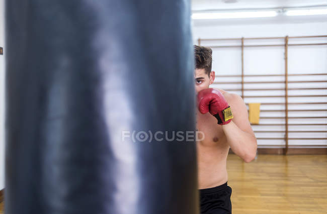 Young guy training in gym with punch bag — Stock Photo