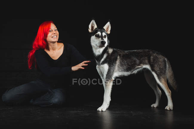 Portrait of young woman sitting on floor with puppy of Siberian Husky on black background — Stock Photo