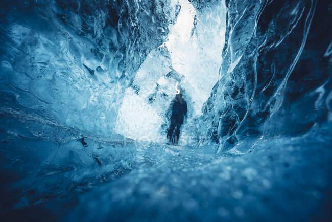 Hombre en hermosa cueva de hielo azul - foto de stock