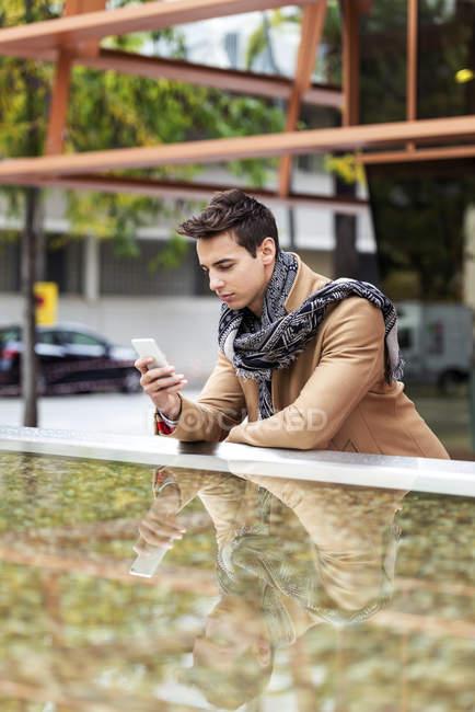 Ritratto di giovane elegante uomo con cappotto in piedi all'aperto e appoggiato alla parete — Foto stock