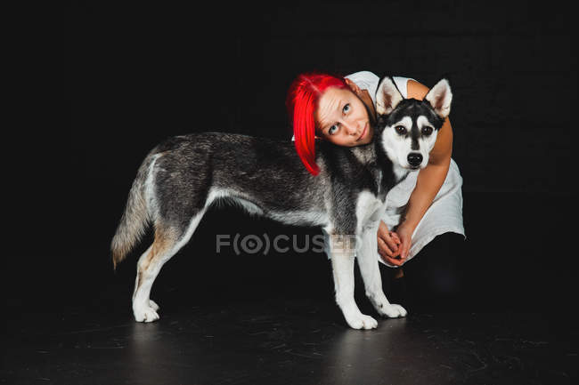 Young woman with bright red hair looking at camera while hugging puppy of adorable Siberian Husky on black background — Stock Photo
