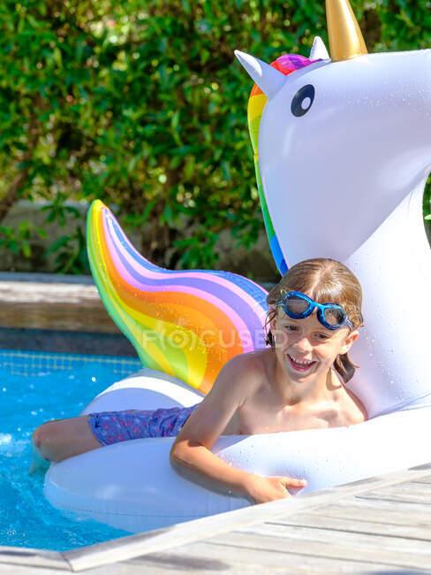 Boy swimming on unicorn float — Foto stock