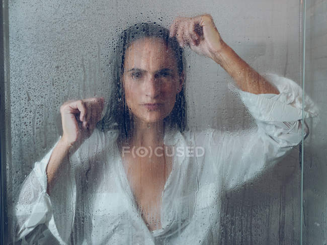 Sopping woman in shirt standing in shower cabin and looking at camera — Stock Photo