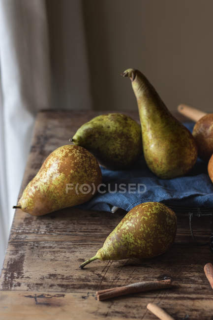 Fresh pears on blue napkin on lumber table in kitchen — Stock Photo