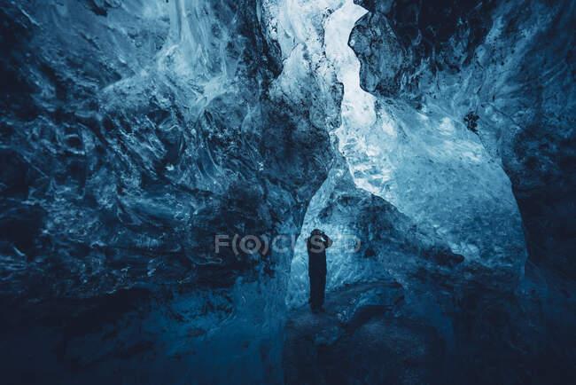 Человек в красивой голубой ледяной пещере — стоковое фото
