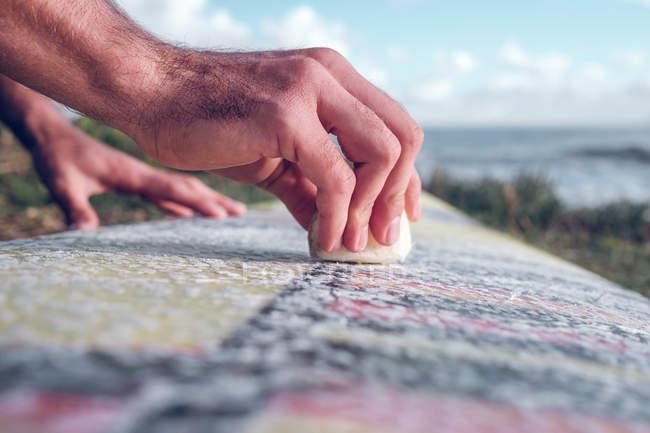 Крупный план мужских рук, распространяющих воск на доске для серфинга на траве возле моря — стоковое фото
