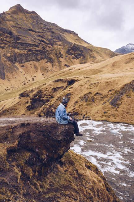 Tipo vista lateral de pie en piedra cerca de río corriente entre montañas marrones en Islandia - foto de stock