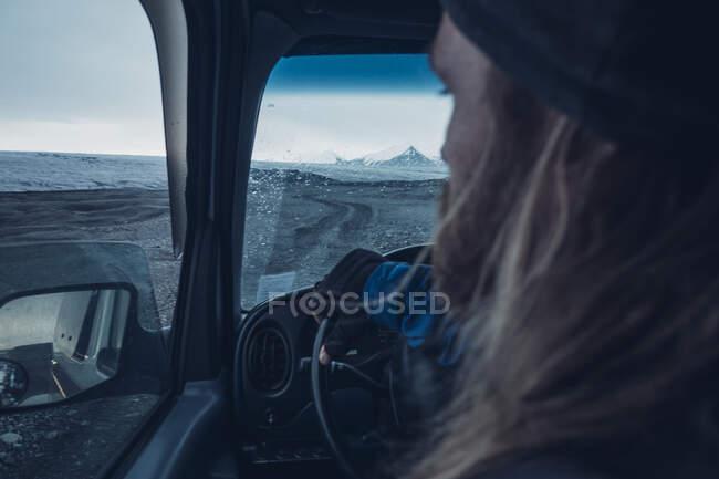 Вид сзади босоногого мужчины, управляющего автомобилем на холодной исландской террасе в сумерках — стоковое фото