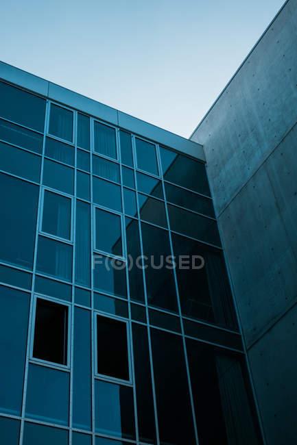 Темные окна современного строительства против голубого неба — стоковое фото