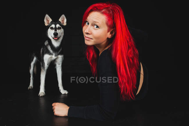 Portrait Of Young Woman Posing On Floor With Bright Red Hair With