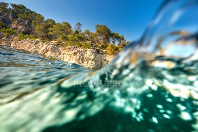 Türkisblauem Wasser und felsigen Klippen mit Bäumen im Hintergrund — Stockfoto