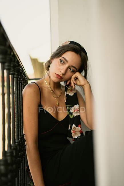 Мрійливий молода леді в елегантне плаття, сидячи на балконі — стокове фото