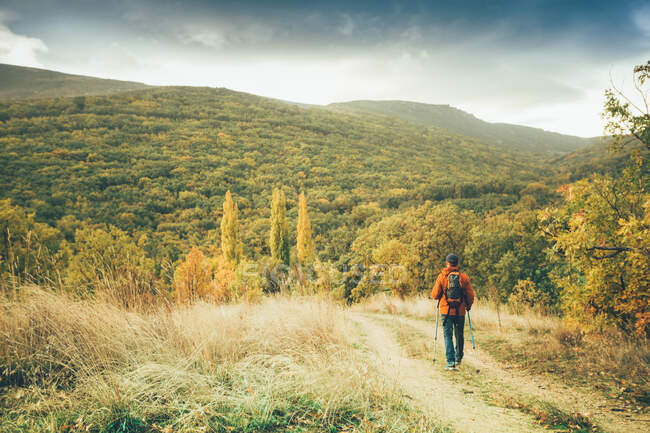 Hiker man on a trail in autumn colors — Stock Photo