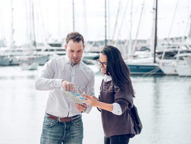 Bonito homem adulto gesticulando com a mão e segurando mapa ao mostrar o caminho para turista feminino no porto — Fotografia de Stock