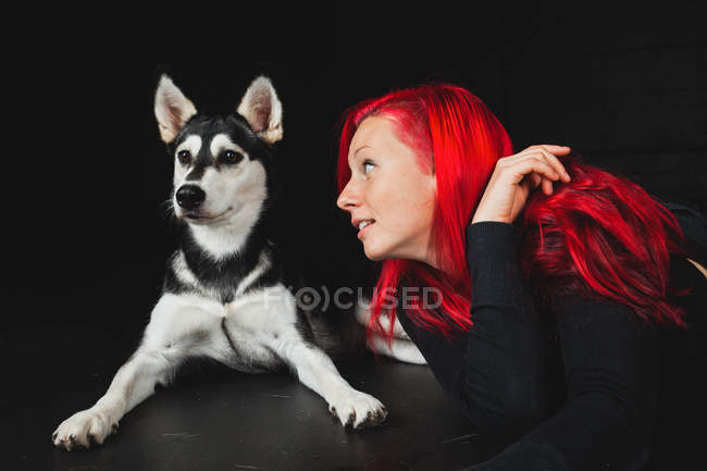 Young woman with bright red hair looking at puppy of adorable Siberian Husky on black background — Stock Photo