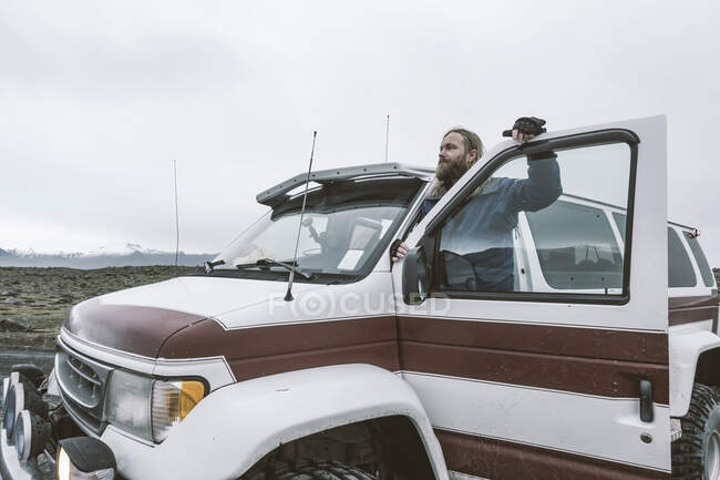 Man with car on remote road in trip — Stock Photo