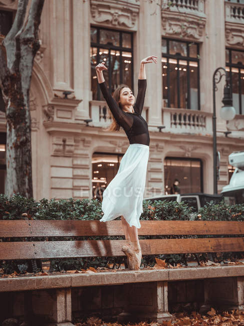 Young attractive ballerina in skirt and blouse upping hands and standing on bench on street — Stock Photo