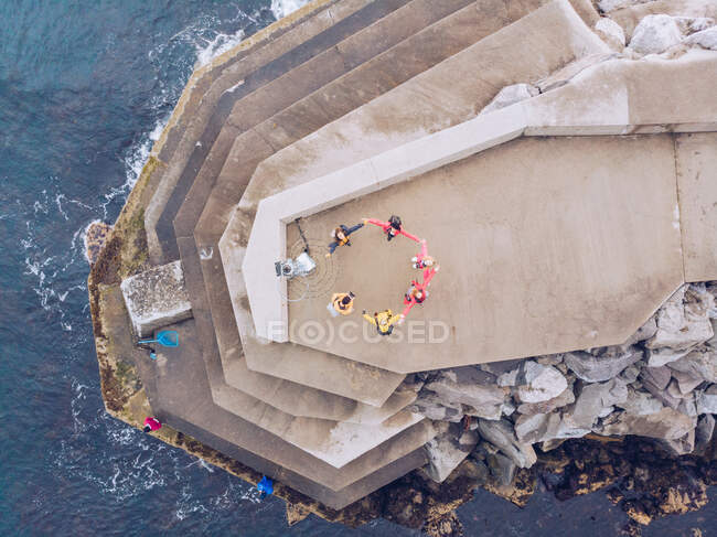 From above shot of anonymous people forming circle while standing on concrete building on amazing rocky cliff near waving sea — Stock Photo