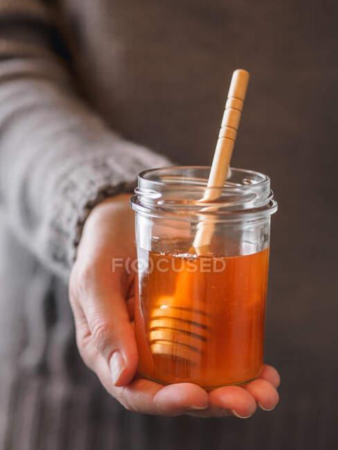 Постріл руки анонімної жінки з маленьким глечиком свіжого меду з ложкою. — стокове фото