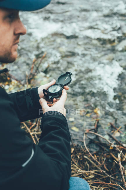 Young man holding a compass in the mountain next to a river with brown color background — Stock Photo