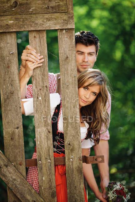 Молода пара в традиційних австрійських вбрання, дивлячись на камеру, поки стоїть біля огорожі в саду — стокове фото