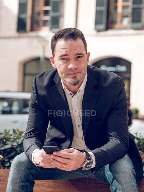 Handsome adult man in elegant jacket holding smartphone and looking at camera while sitting on bench on street — Stock Photo