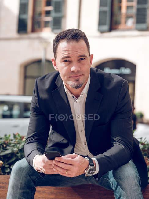 Bel homme adulte en veste élégante tenant smartphone et regardant la caméra tout en étant assis sur le banc sur la rue — Photo de stock