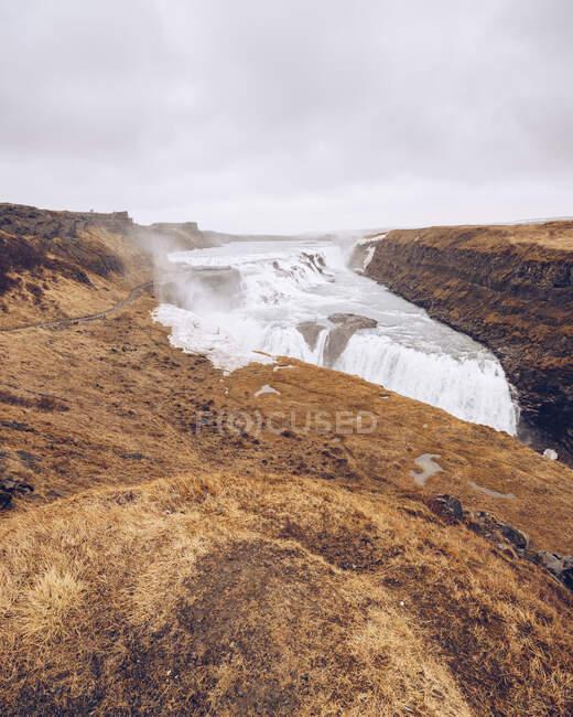 Grande cascata de água fluindo entre terras mortas e caindo entre rochas na Islândia — Fotografia de Stock