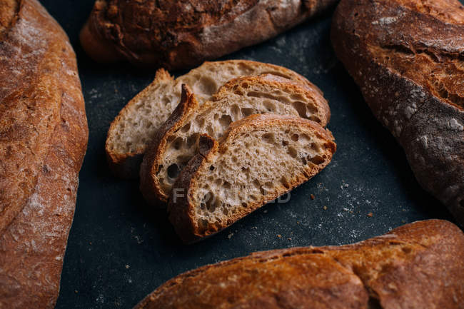 Homemade rustic bread loaves with slices on dark background — Stock Photo
