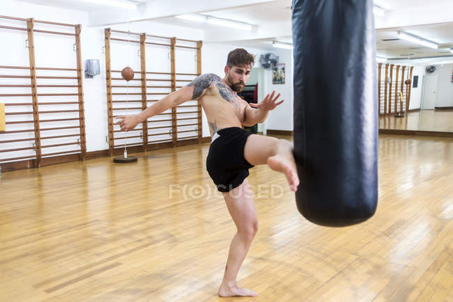 Kickboxing fighter training in gym with punch bag — Stock Photo