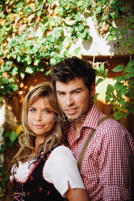 Young couple in traditional Austrian outfits posing in garden — Stock Photo