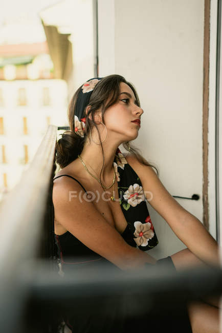 Dreamy young lady in elegant dress sitting on balcony — Stock Photo