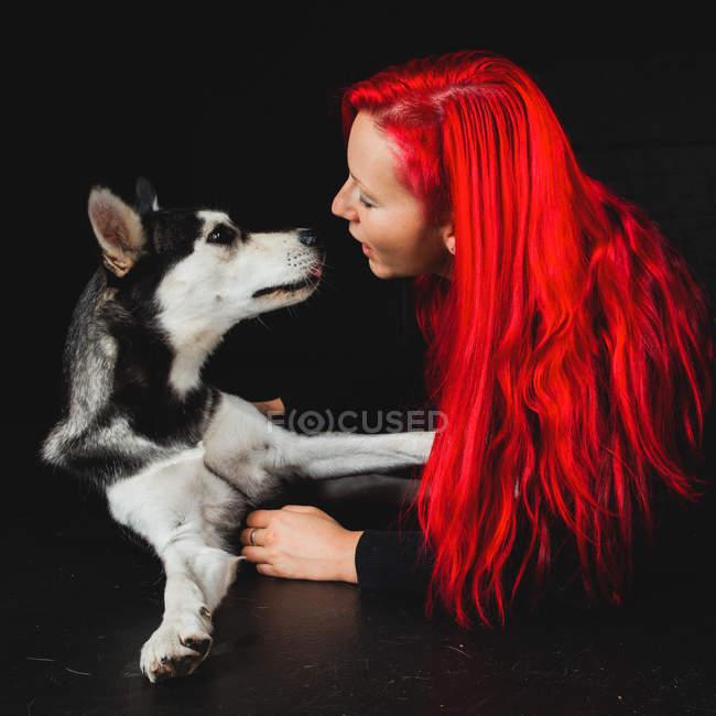 Jeune femme avec les cheveux rouge vif regardant chiot de mignon Siberian Husky — Photo de stock