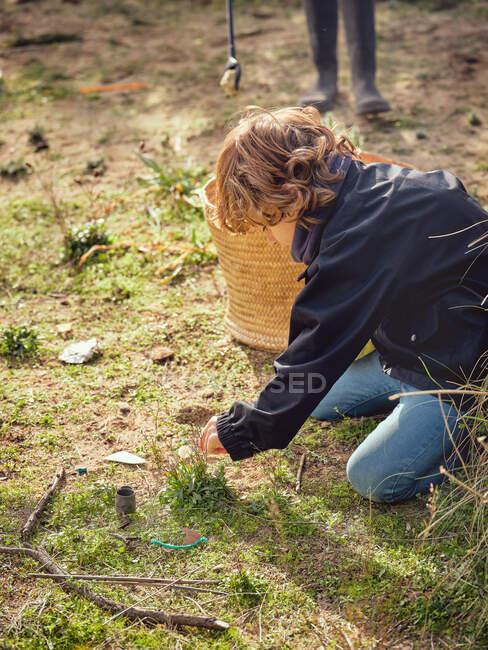Niño con montón de basura en las manos cerca de la cesta - foto de stock