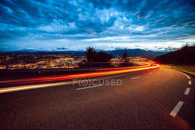Vue des lumières du sentier lumineux sur la route en soirée à la campagne sur fond de ville et ciel nuageux — Photo de stock